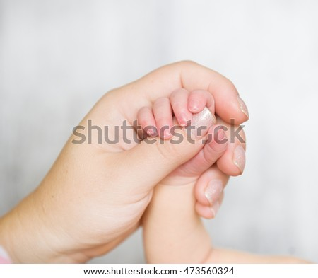 Newborn baby hand in mom's hand