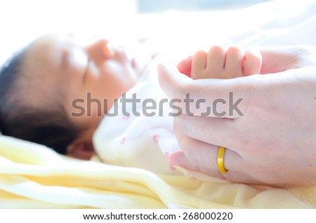 Newborn baby holding mother's hand.
