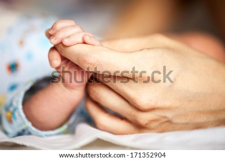 Newborn baby holding mother's hand, image with shallow depth of field  - stock photo