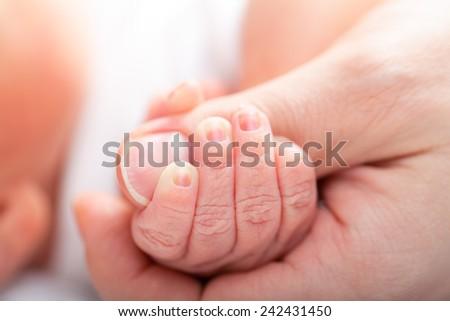 Newborn baby holding mother's thumb - stock photo