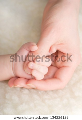 Newborn baby holding mothers finger - stock photo