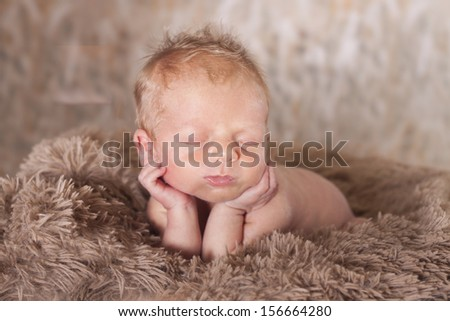 newborn baby in a cute pose for his portraits. Hands under chin resting.