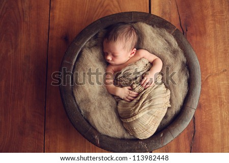 Newborn baby in a round wood bowl - stock photo