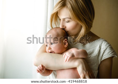 newborn baby in a tender embrace of mother at the window. mother holding a small child in the window - stock photo
