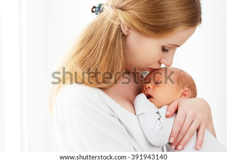 newborn baby in a tender embrace of mother at window - stock photo