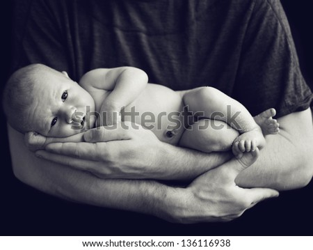 Newborn baby in dad's hands - stock photo