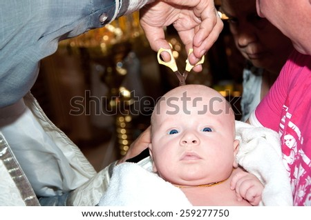 Newborn baby in font with hands of priest. baby christening. hair cutting scissors hands of the priest. Ceremony of a christening in Christian church  - stock photo