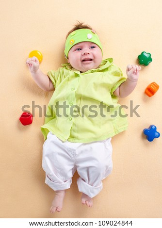 Newborn baby in green chemise and headband on yellow background