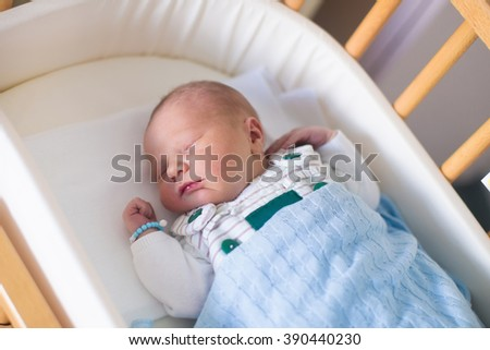 Newborn baby in hospital room. New born child in wooden co-sleeper crib. Infant sleeping in bedside bassinet. Safe co-sleeping in a bed side cot. Little boy taking a nap under knitted blanket. - stock photo