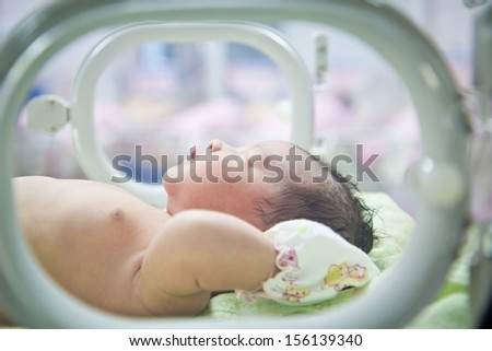 newborn baby in Incubator care at nursery - stock photo