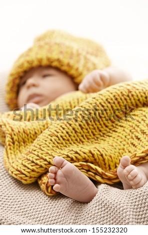 Newborn baby in knitwear. Focus on barefoot. - stock photo