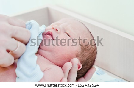 newborn baby in maternity hospital looking at the camera