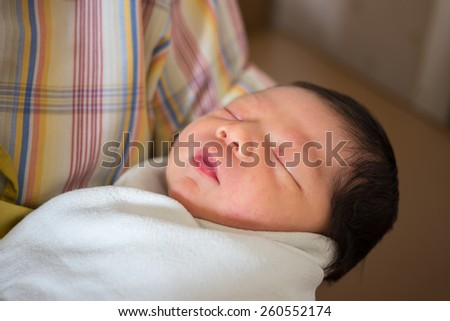 Newborn baby in mother embrace. - stock photo
