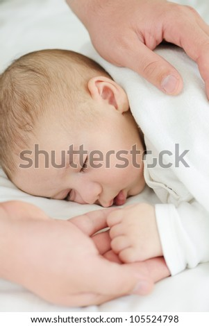 Newborn baby in mother's hands sleeping on bed