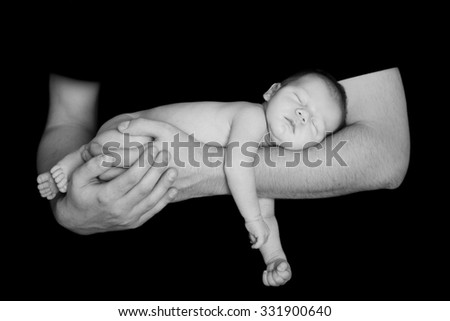 Newborn baby in the comfort and protection of his fathers arms