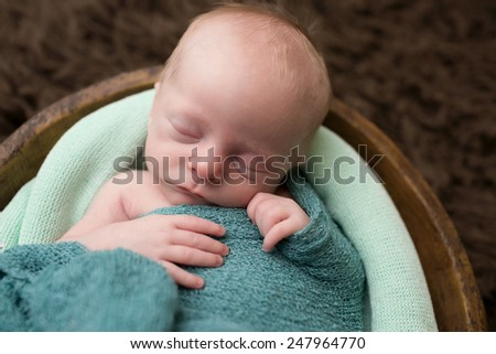 Newborn baby, infant, sleeping in a bowl, nap or childcare concept - stock photo