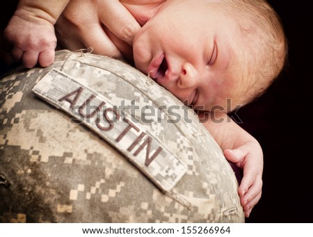 Newborn baby is laying on army helmet - stock photo