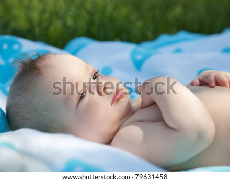 Newborn baby lay on towel in park