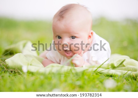 Newborn baby laying on the grass put out tongue - stock photo