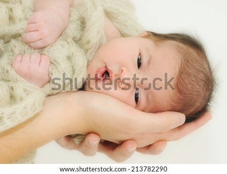 newborn baby laying on the mother's hands