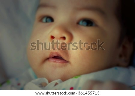 newborn baby looking at the camera