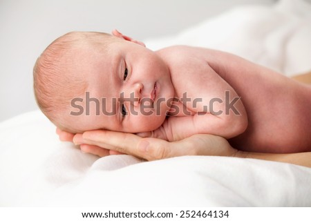 newborn baby lying down on mother's hands face closeup body care maternity caucasian white - stock photo
