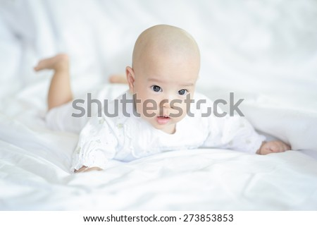 Newborn baby lying in bed.