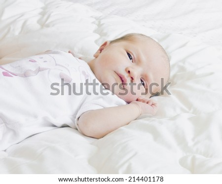 newborn baby lying in his crib, and closely monitoring.copy space background - stock photo