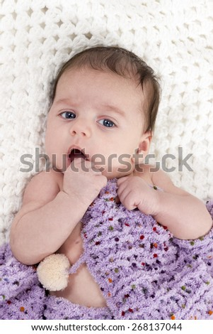 Newborn baby lying on a knitted blanket covered and holds his hand to his mouth