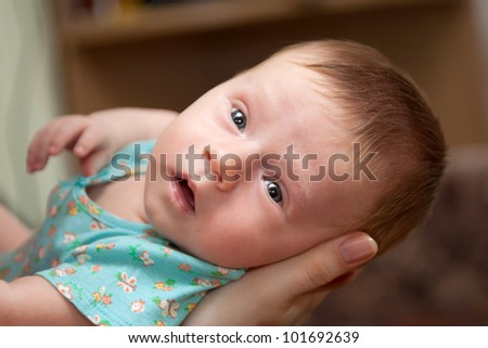 Newborn baby lying on his mother's arms and looking into the camera. Focus on the baby's face
