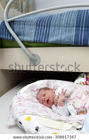 Newborn baby lying on the bed at home