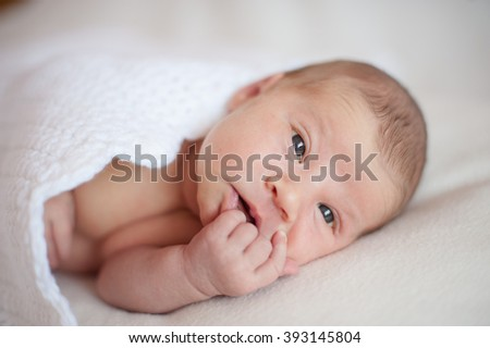 Newborn baby lying under a warm blanket, and looks into the distance
