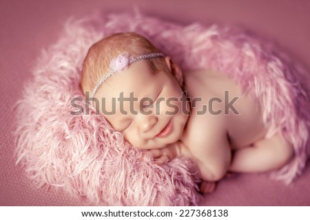Newborn baby on a pink fluffy blankets