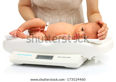Newborn baby on a weight scale  - stock photo