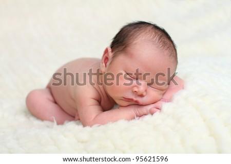 Newborn baby on sheep's wool - stock photo