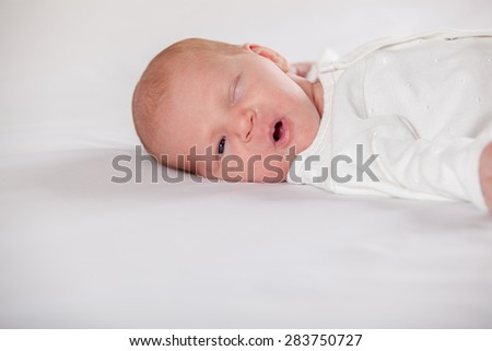 Newborn baby peacefully sleeping, on a white background