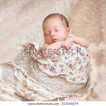 Newborn baby peacefully sleeping on blanket - stock photo