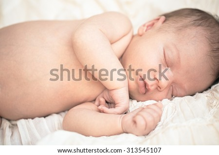 Newborn baby peacefully sleeping on blanket