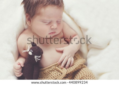 Newborn baby peacefully sleeping. picture of a newborn baby curled up sleeping on a blanket. Newborn baby is sleeping - stock photo