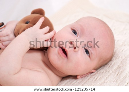 Newborn baby playing with toys - stock photo