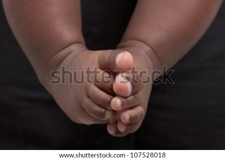 Newborn baby's feet. A closeup with a candid appeal. The baby skin is african brazilian tone. - stock photo