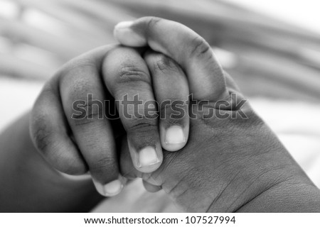 Newborn baby's hand. A closeup with a candid appeal. The baby skin is african brazilian tone. - stock photo