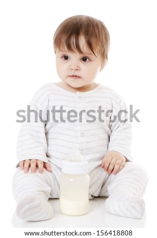 Newborn baby sitting on the floor with the bottle. Isolated on white. - stock photo