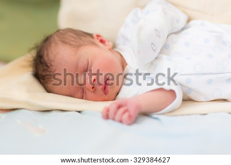 Newborn baby sleeping, 3 days old at home, soft focus,shallow DOF