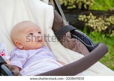 Newborn baby sleeping in a bouncer in the garden - stock photo