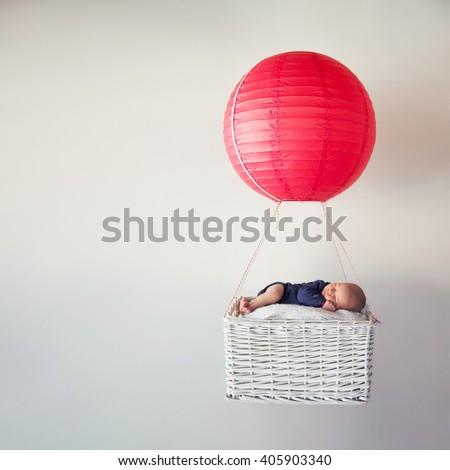 Newborn baby sleeping in a tiny air balloon basket - stock photo