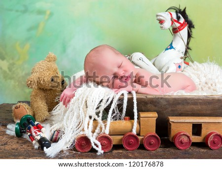 Newborn baby sleeping in a trench bowl surrounded by vintage antique toys - stock photo
