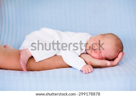 Newborn baby sleeping in arms of his father. Dad holding new born son. Child taking a nap on parent hand. Infant kid sleeping on a blue blanket. Textile bedding for kids. Parents and children bonding. - stock photo