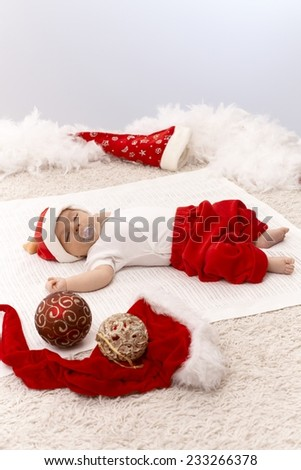 Newborn baby sleeping in Santa hat among christmas ornaments. - stock photo