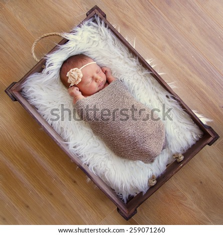 Newborn baby sleeping in vintage crate, wearing flower headband - stock photo